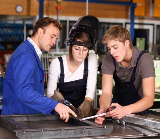 patron d'entreprise entrain de transmettre son savoir à de jeunes apprentis