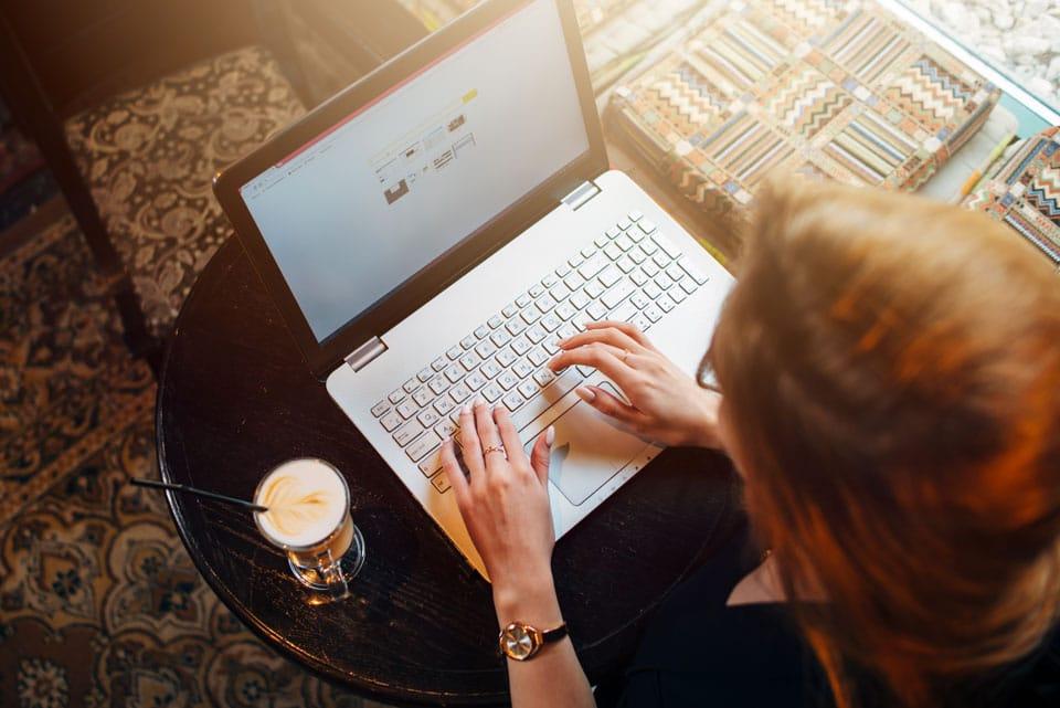 jeune femme avec un ordinateur laptop entrain de travailler dans un café