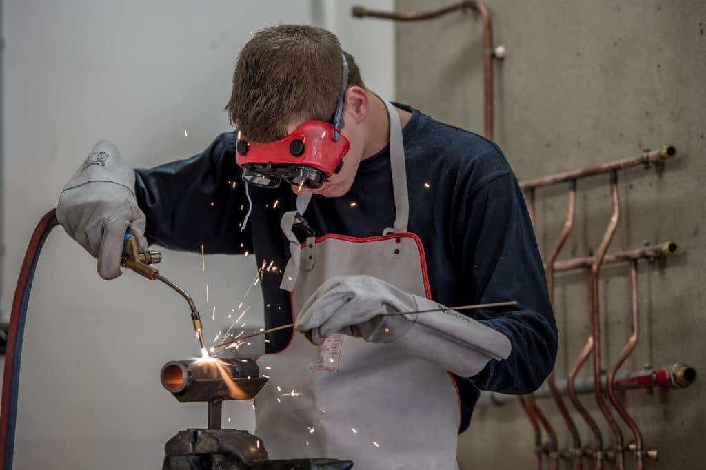 un jeune apprenti entrain de souder un tube d'acier