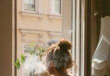 jeune femme fumant à la fenêtre